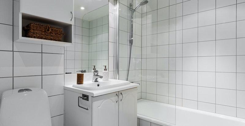 Flislagt bad med god plass for både vaskemaskin og tørketrommel.