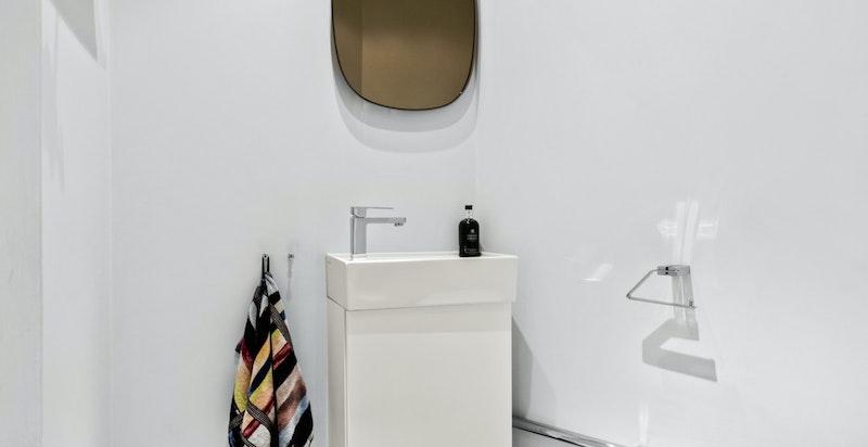 Toalettrommet har vegghengt wc og servantskap - perfekt for gjester.