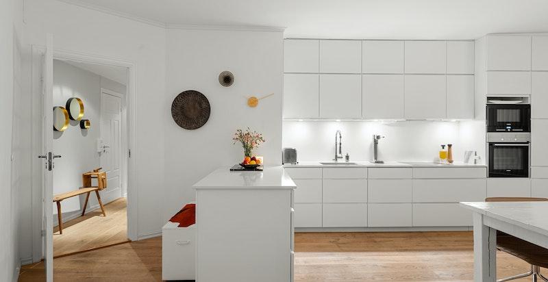 Kjøkkenet er utstyrt med kompositt benkeplate, samt integrerte hvitevarer som komfyr, induksjon platetopp, oppvaskmaskin, mikroovn og to kjøl/frys fra Siemens.