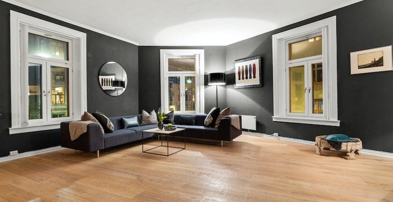 Innbydende stue med store, klassiske vinduer i tre retninger som slipper inn rikelig med naturlig sollys.