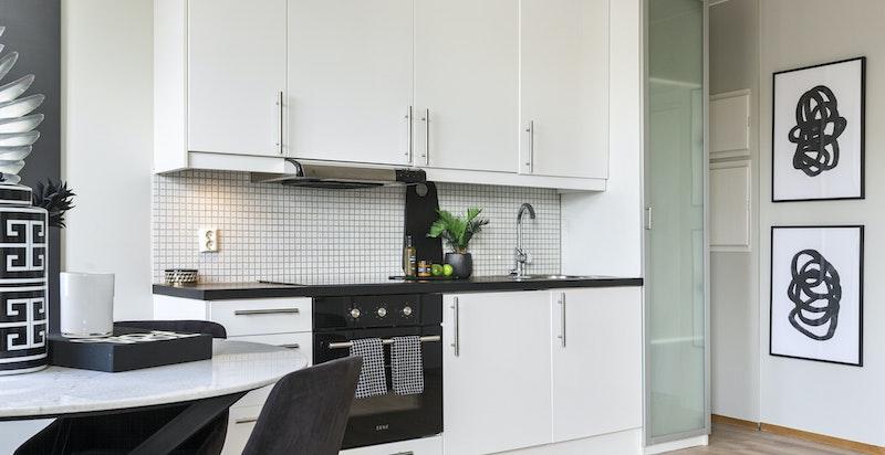 Kjøkken med oppdatert kjøkkenbenk og ny stekeovn (2021). Mosaikkfliser over benk.