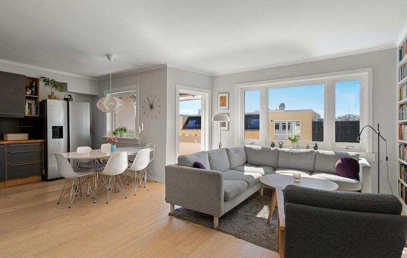 Stor, lys og luftig stue med plassbygde bokhyller og utgang sydvestvendt balkong