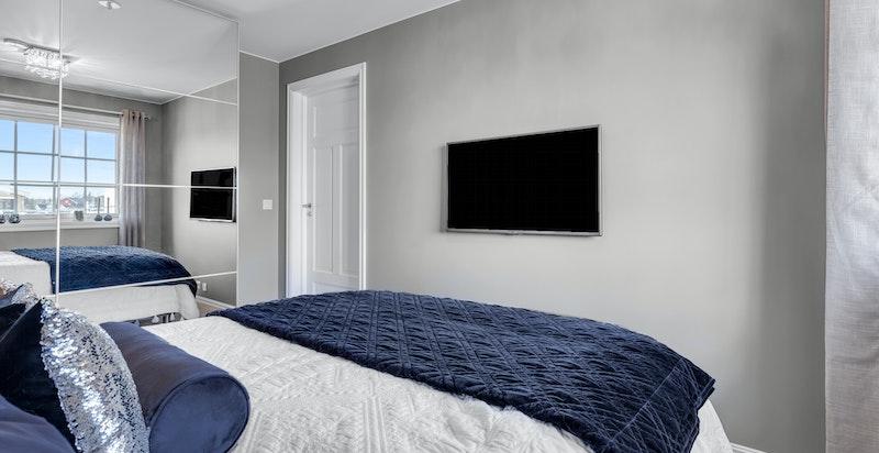 Soverommet er innredet med stor skyvedørsgarderobe med speilfronter.