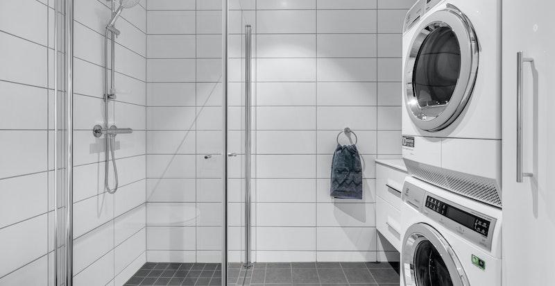 Delikat flislagt bad 1 i 1. etasje med moderne innredning, dusjhjørne og opplegg til vaskemaskin/tørketrommel.