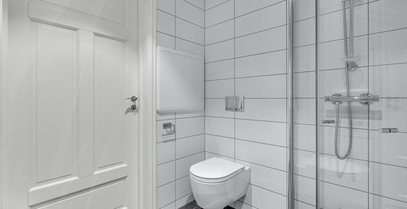 Det er vegghent toalett. Badet har en praktisk plassering i gangen i 1. etasje.
