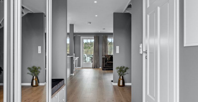 Entreen gir et meget godt førsteinntrykk av boligen med delikate fliser på gulv med varme og downlightsbelysning i himling.