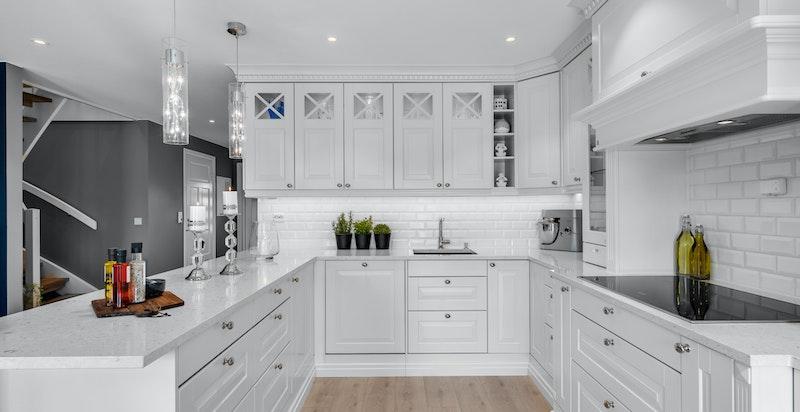 Rålekkert og påkostet kjøkken fra Sigdal med hvite profilerte fronter og stein benkeplate i elegant kombinasjon.
