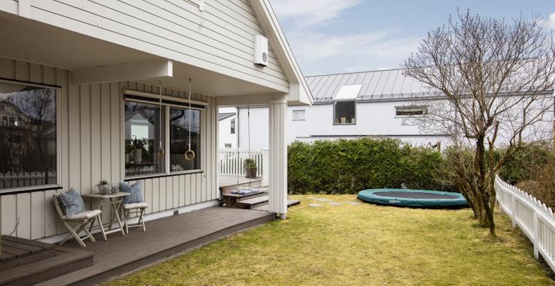 Det er utgang fra kjøkkenet til terrassen som strekker seg langs huset på hagesiden