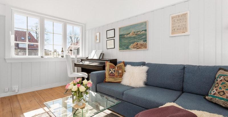 Stuen har store, klassiske vinduer som slipper inn rikelig med naturlig sollys.