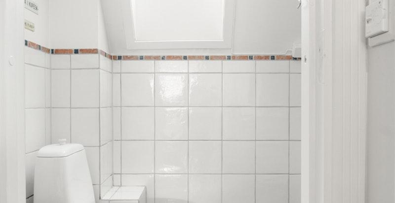 Bad med wc, servant med skuffer under, dusj i innmurt badekar og vaskemaskin (medfølger).