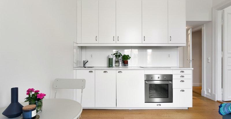 IKEA kjøkkeninnredning fra 2017 med laminat benkeplate, og plate over benk. I tillegg er det integrert komfyr, platetopp, oppvaskmaskin og kjøleskap.