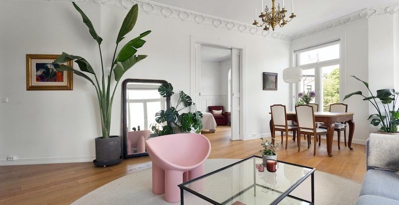 Leiligheten har en gjennomgående planløsning med store, klassiske vinduer som slipper inn rikelig med naturlig sollys.