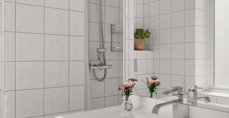 Badet er utstyrt med vegghengt wc, servant og dusj i hjørne.
