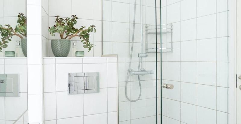 Videre er badet utstyrt med vegghengt wc og servant dusj i hjørne med glassdør/veggdører.
