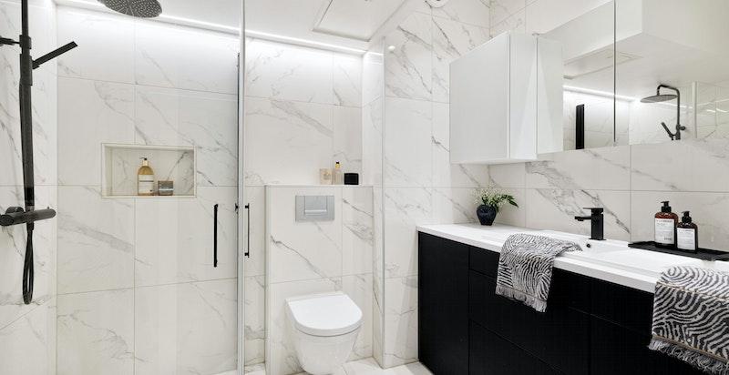 Lekkert bad fra 2018 med tidløse marmorfliser, god plass og speisaltilpasset belysning