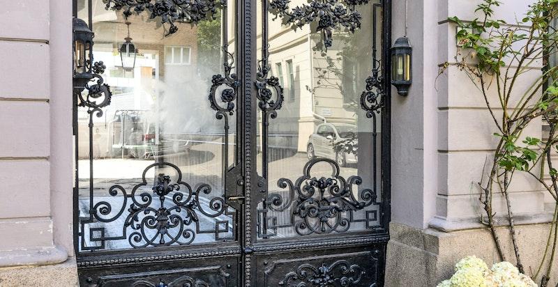 Vakkert inngangsparti med port i smijern og glass