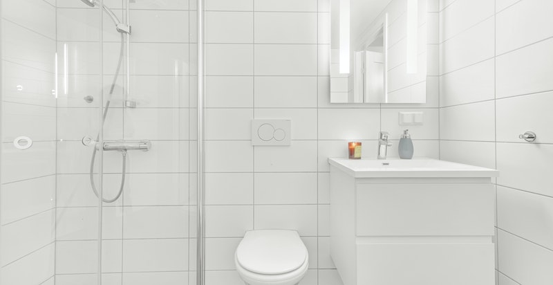 På veggene er det hvite rektangulære fliser og på gulvet er det grå fliser på 10x10 cm