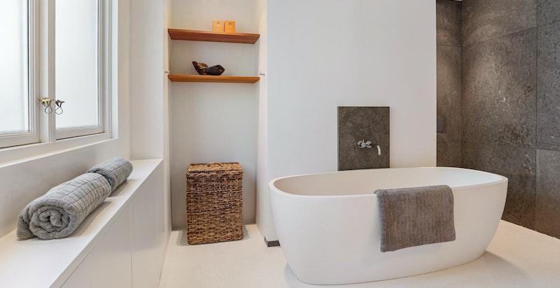 Stort badeværelse med vindu, badekar, dusjnisje og wc
