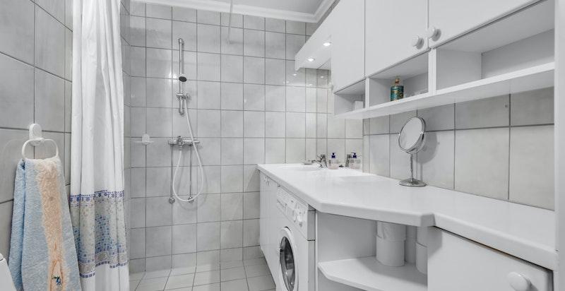 Flislagt bad med varmekabler i gulv, dusjhjørne, toalett, ventil/avtrekk i vegg, stor benkeplate med servant og blandebatteri. Opplegg til vaskemaskin