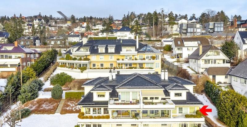 Fasaden sett direkte fra syd. Leiligheten ligger én etg. opp fra bakkeplan, helt til høyre i bildet