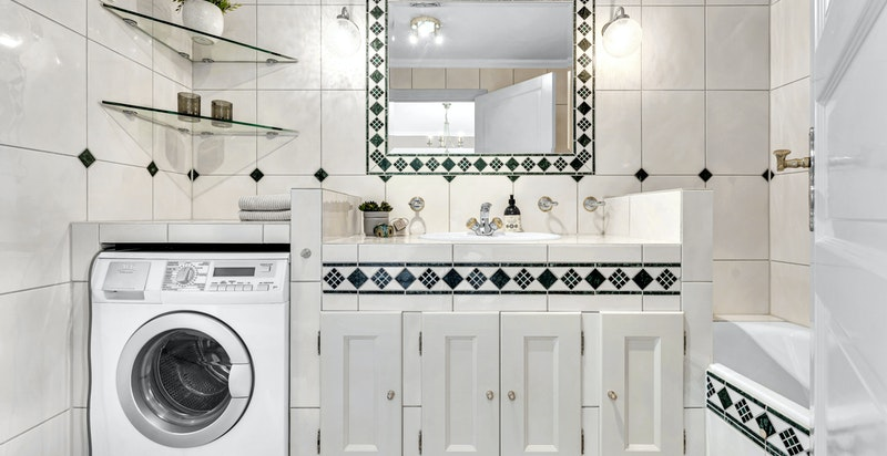 Bad/wc innenfor hovedsoverom innredet med badekar, varmekabler under flis i gulv, downlights, toalett, ventil i himling, opplegg til vaskemaskin