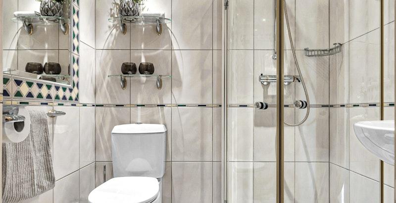 Dusjbad/wc ved gang innredet med dusjhjørne med innfellbare dusjdører, varmekabler i gulv, downlights, toalett, veggmontert servant med blandebatteri, ventil i himling