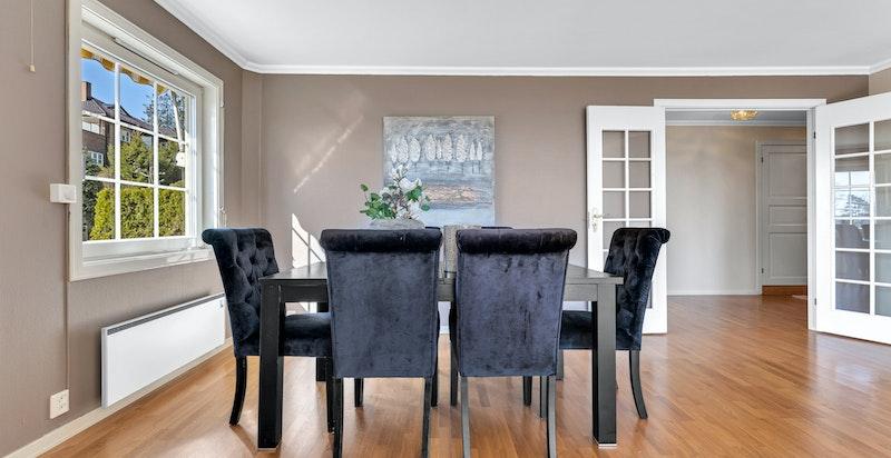 Plass til stort spisebord. Kjøkkenet er vegg-i-vegg med spisestuen