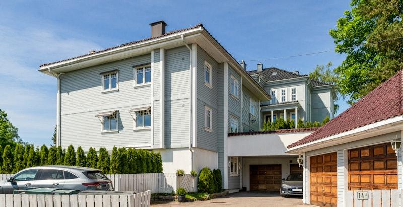 Fasade fra Ivar Aasens vei - Innkjøring til garasje og gjesteparkering til venstre på gårdsplassen