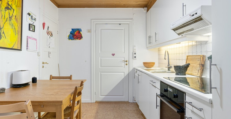 Kjøkkeninnredningen i hybeldelen består av hvite, glatte fronter med laminat benkeplate og nedfelt oppvaskkum