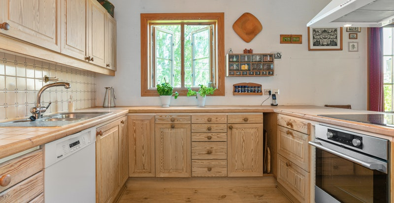 Kjøkkeninnredning fra byggeår med hvitpigmenterte furufronter på skuffer og under-/overskap