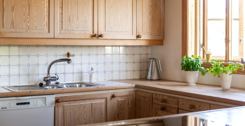 Flislagte benkeplater og benkeplater i furu og fliser på vegg mellom benk og overskap
