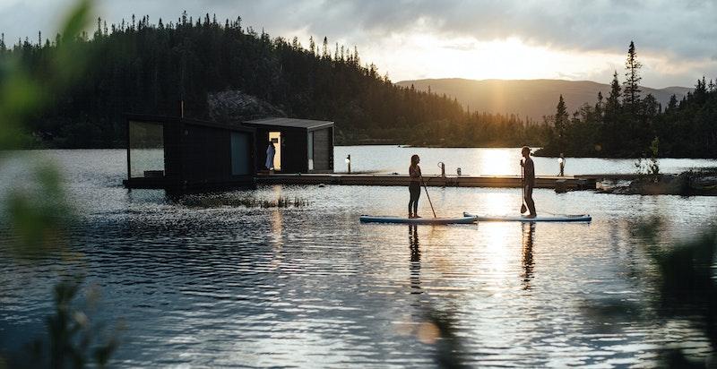 Ta en SUP- eller kanotur på Kvitåvatn. De flytende badstuene i bakgrunnen
