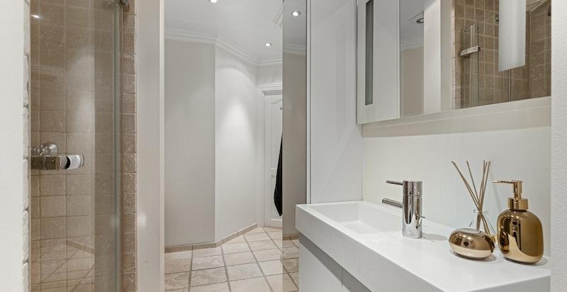 Pent flislagt baderom med dusjnisje og wc.