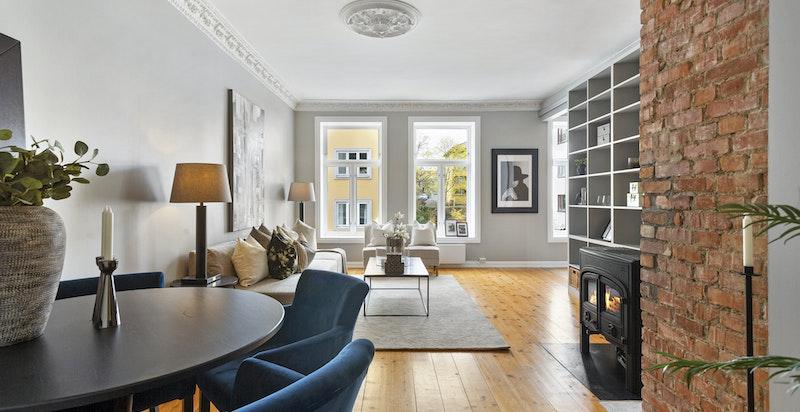 Stor og lys stue med sjenerøse vindusflater, rosetter og stukkatur. Lune tregulv og peisovn.