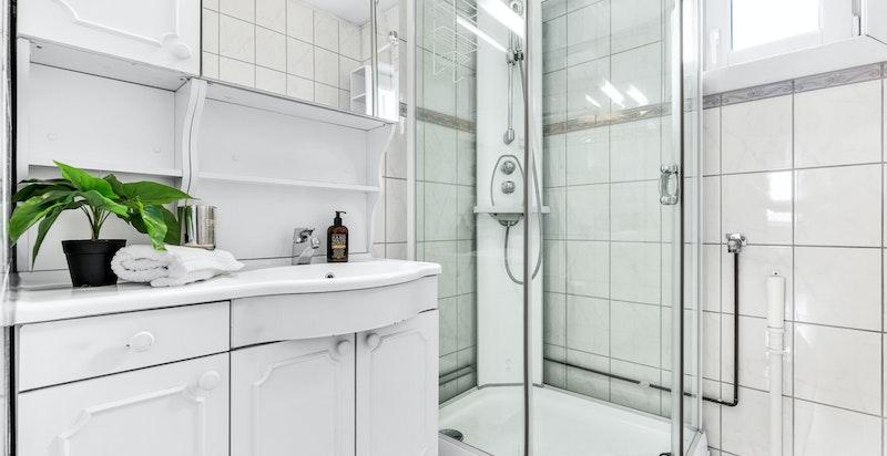 Flislagt bad med varmekabler i gulv. Innredningen består av servant med underskap og blandebatteri, dusjkabinett