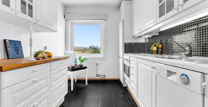 Separat kjøkken med innredning bestående av profilerte fronter med stålhåndtak, heltre og laminat benkeplater, to stålkummer med blandebatteri