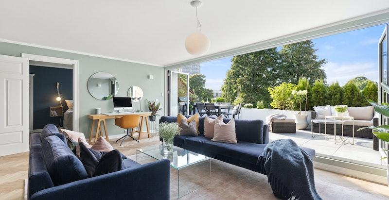Hele veggen er en foldedør og her kan man inkludere terrassen i leiligheten på solrike sommerdager.