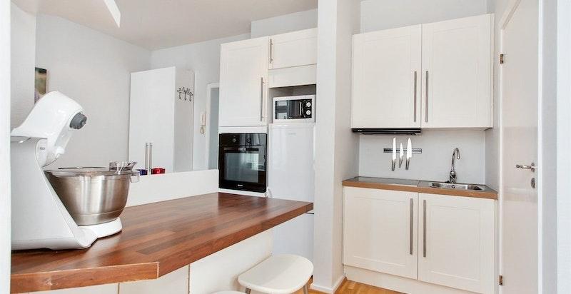 Godt med oppbevaringsplass på kjøkkenet. Det er laget en praktisk barløsning med sitteplass