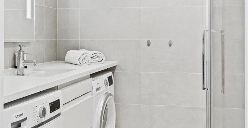 Det er opplegg til vaskemaskin og tørketrommel under benk.