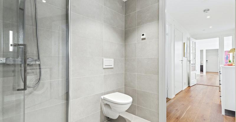 Dusjhjørne med innfellbare dusjvegger og vegghengt toalett.