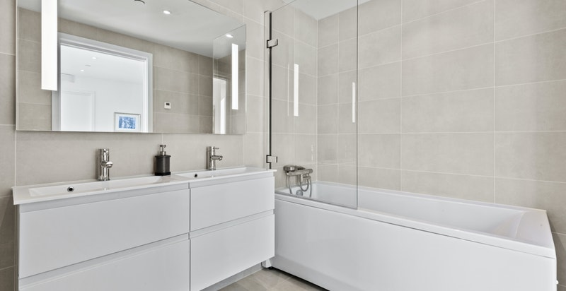 Flott baderomsinnredning med dobbel vask over skuffer, ettgreps blandebatteri og speil med innfelt belysning.