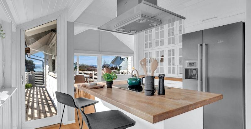 - Kjøkkeninnredning med hvite profilerte fronter på skuffer og skap -