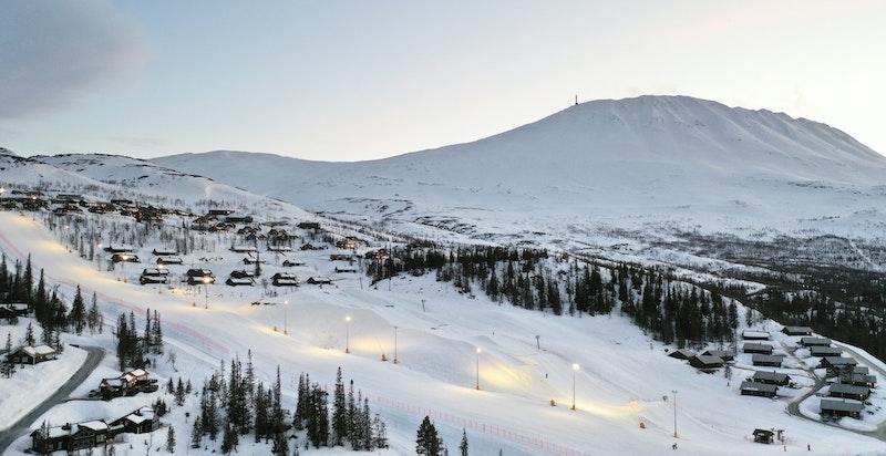 Hovdetun med 9 fritidsboliger til venstre over parken og alpinbakken med lys i Gausta skisenter