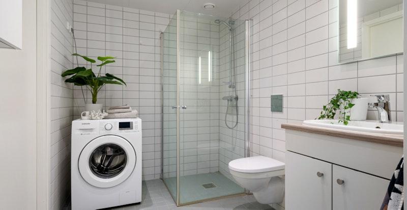 Romslig og delikat flislagt baderom med varmekabler og opplegg for vaskemaskin og kondenstrommel.