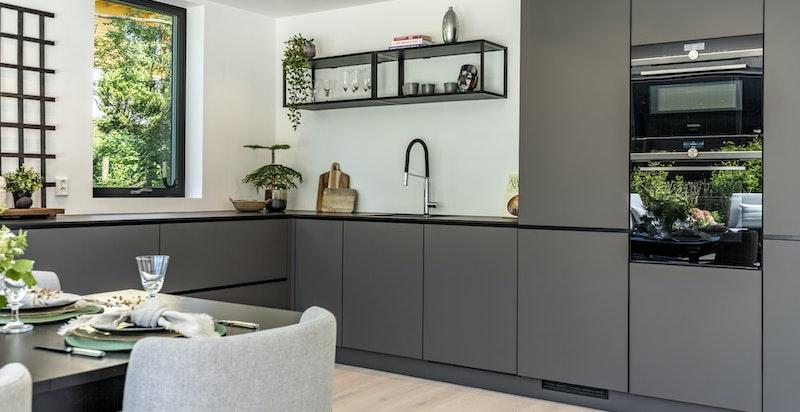 Godt utstyrt KVIK-kjøkken med integrerte hvitevarer som kjøleskap m/frys, komfyr, induksjonstopp med integrert avtrekksvifte, mikrobølgeovn og oppvaskmaskin.