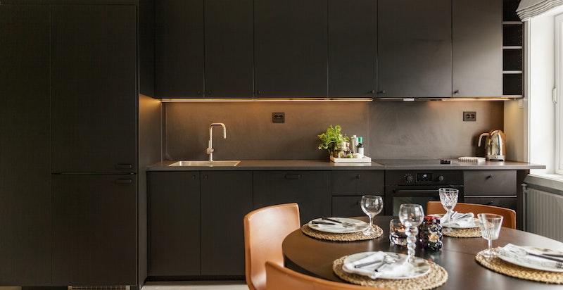 Innredningen består av laminat benkeplate og plate over benk, samt nedfelt kum og kullfiltervifte. Integrerte hvitevarer som komfyr, platetopp, oppvaskmaskin og kjøl/frys.