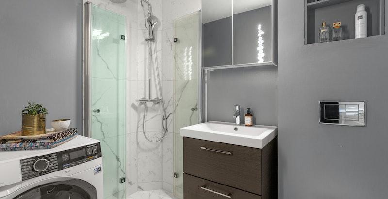 Delikat og tidløst baderom i praktisk tilknytning til både entré og boligens soverom.