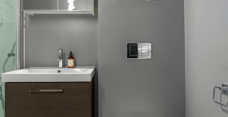 Badet er utstyrt med behagelige varmekabler, samt vegghengt wc, servant med skuffer og speil over og dusj i hjørne med innadslående dører.