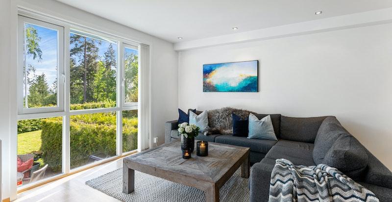 Salong i stue med store vinduer som gir mye naturlig lys og hyggelig utsyn til grøntarealene