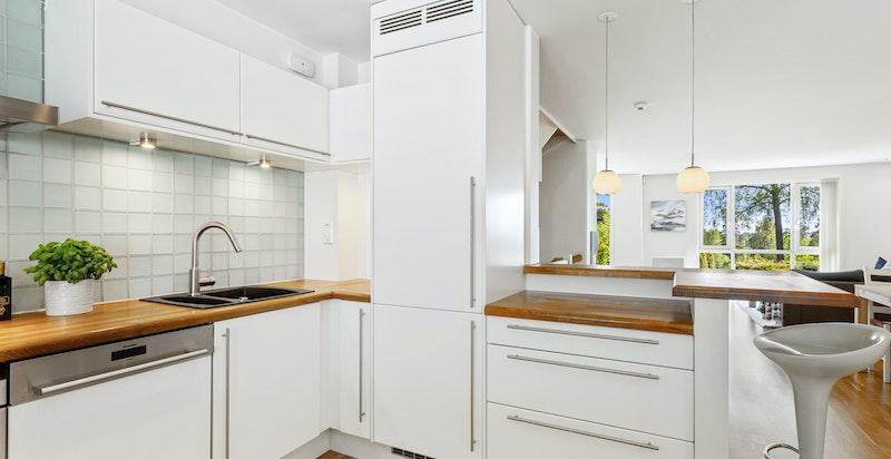 Integrerte hvitevarer og glasskeramisk koketopp. Stilfull heltre benkeplate og hvit kjøkkeninnredning med glatte fronter